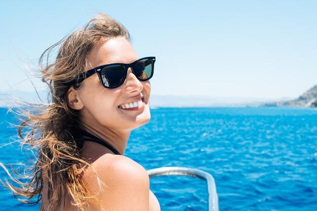 Turista femminile felice che ha divertimento sulla barca a vela. vacanze estive in barca a vela. bella donna all'aperto in bikini Foto Premium