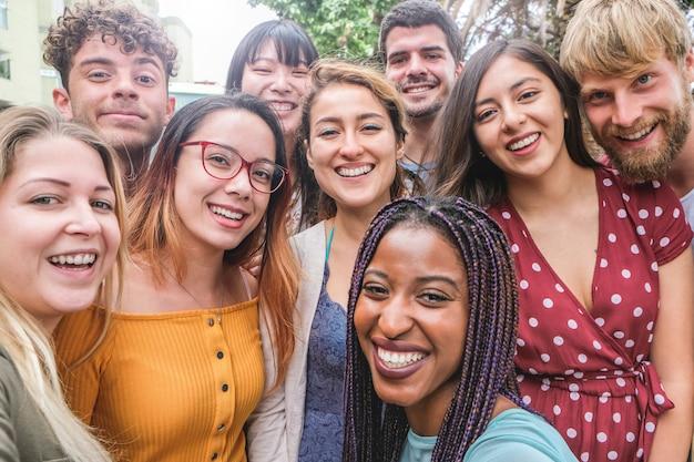 Amici felici di diverse culture e razze che scattano foto facendo facce buffe - generazione millenaria e concetto di amicizia con i giovani che si divertono insieme - focus principale sulla ragazza con gli occhiali Foto Premium