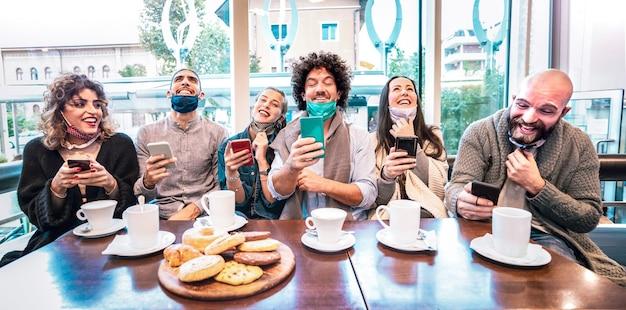 Amici felici che utilizzano telefoni cellulari intelligenti al bar Foto Premium