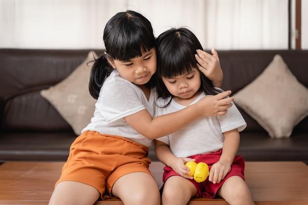 Sorelle divertenti felici della ragazza due che abbracciano e che ridono con l'amore Foto Premium