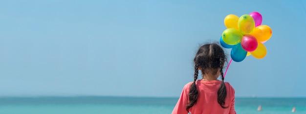 Ragazza felice che tiene gli aerostati di aria colorati sulla spiaggia. vacanze estive Foto Premium