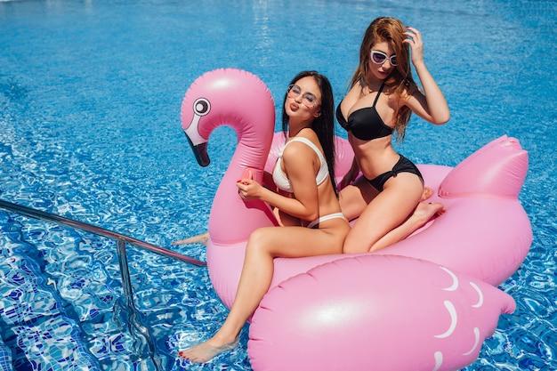 Ragazze felici con belle figure si divertono sui fenicotteri gonfiabili in piscina Foto Premium