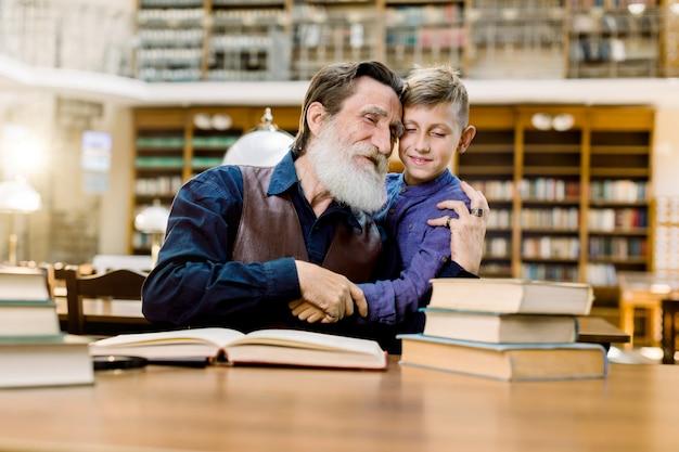 Felice nonno e nipote si abbracciano mentre trascorrere del tempo insieme nella vecchia biblioteca vintage, leggendo libri Foto Premium