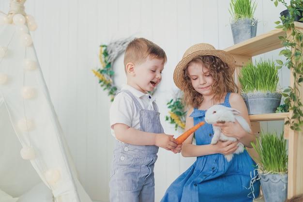 Bambina e ragazzo di risata felici che giocano con un coniglio del bambino Foto Premium