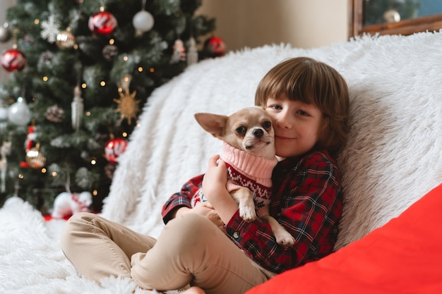 Il ragazzino felice abbraccia il cane a natale Foto Premium