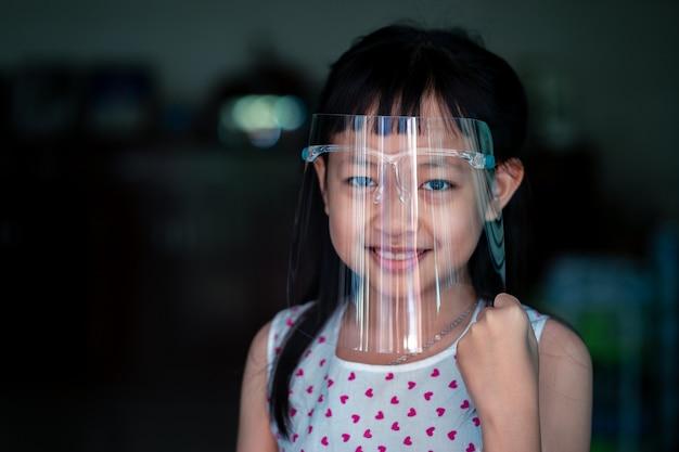 Felice bambina bambino con una visiera in plastica per una maschera di protezione dai virus sul viso Foto Premium