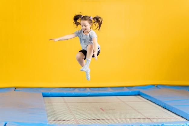 Bambina felice che salta sul trampolino nel centro fitness Foto Premium