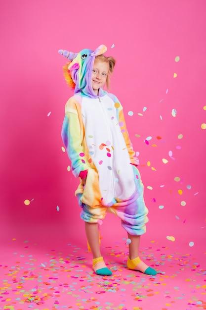 La bambina felice nell'unicorno di kigurumi su una parete rosa si rallegra in coriandoli multicolori Foto Premium