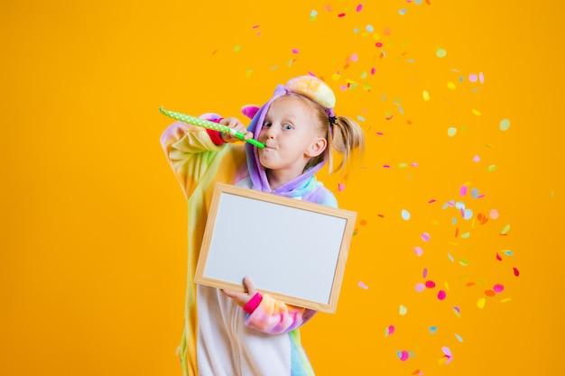 Una bambina felice in un kigurumi unicorno tiene una scheda vuota per il testo su un muro giallo Foto Premium