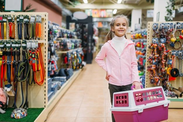 Bambina felice con trasportino per gatto nel negozio di animali Foto Premium