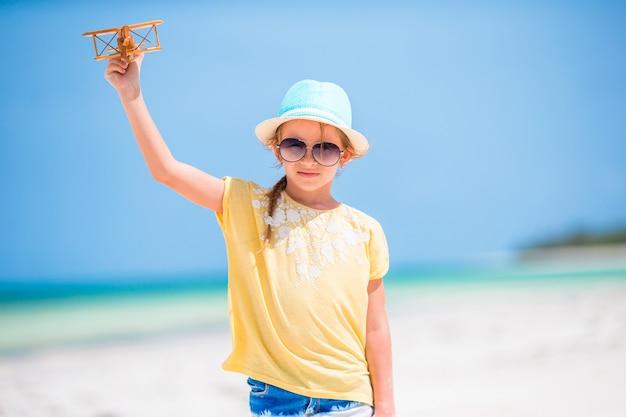 Bambina felice con l'aeroplano giocattolo in mani sulla spiaggia bianca Foto Premium