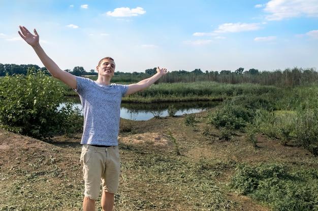 Uomo felice respirando aria fresca profondamente in piedi contro il lago e il campo una giornata di sole Foto Premium