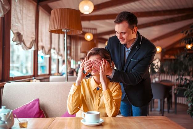 L'uomo felice chiude le mani degli occhi alla bella donna nel ristorante. appuntamento romantico di coppia d'amore Foto Premium