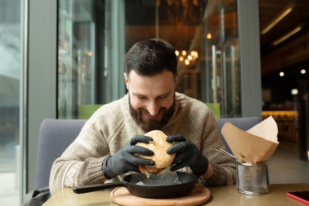 Uomo felice che mangia hamburger nel ristorante Foto Premium