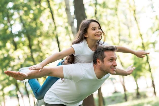 Uomo felice che dà sulle spalle alla sua bella figlia con le braccia tese nel parco Foto Premium