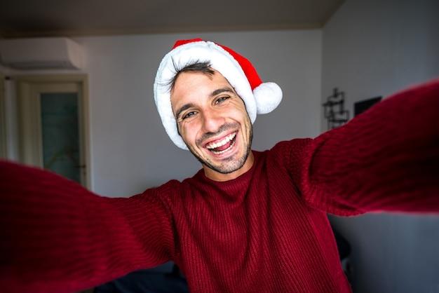 Uomo felice con il cappello di babbo natale prendendo un selfie a casa Foto Premium
