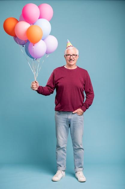 Uomo maturo felice in protezione di compleanno e abbigliamento casual che tiene palloncini mentre posa sulla parete blu Foto Premium