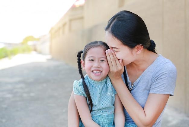 Mamma felice che sussurra qualcosa di segreto al suo piccolo orecchio da figlia. Foto Premium