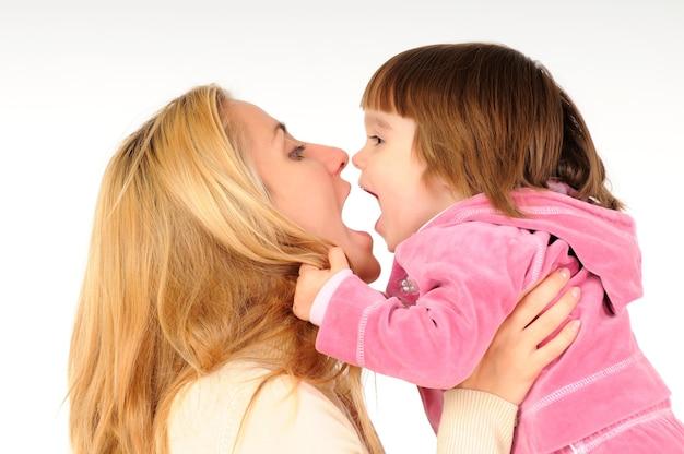 Madre felice che tiene e che gioca con la sua piccola figlia in vestiti rosa sopra bianco Foto Premium