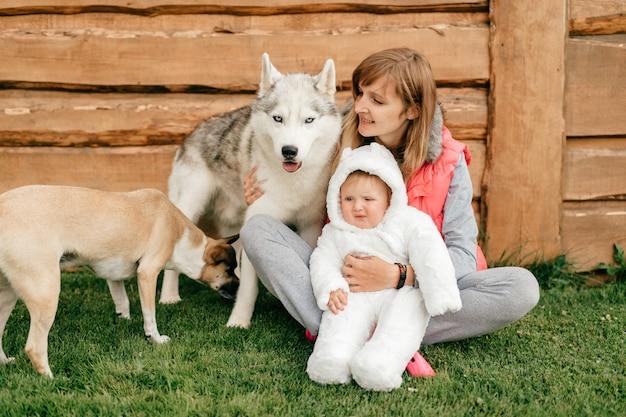 Madre felice che si siede sull'erba e che tiene il costume divertente dell'orso del bambino insieme a due bei cani Foto Premium