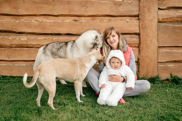 Madre felice che si siede sull'erba e che tiene neonato divertente in costume dell'orso rossastro insieme a due bei cani. Foto Premium