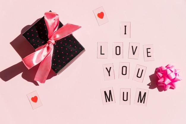 Messaggio di happy mothers day con i cuori rossi su fondo rosa luminoso concetto della cartolina d'auguri. messaggio di mothers day. regalo e testo Foto Premium