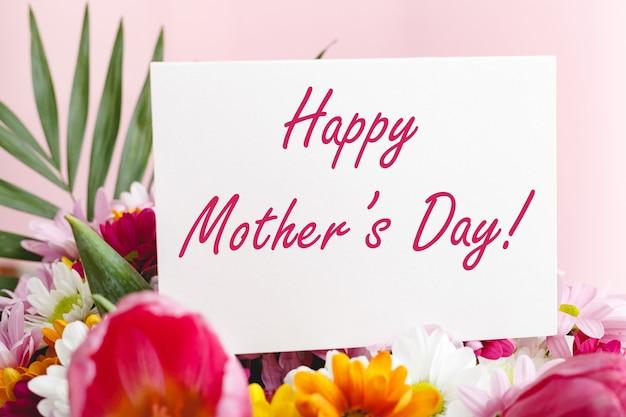 Testo di happy mothers day sulla carta regalo in bouquet di fiori su sfondo di colore rosa Foto Premium