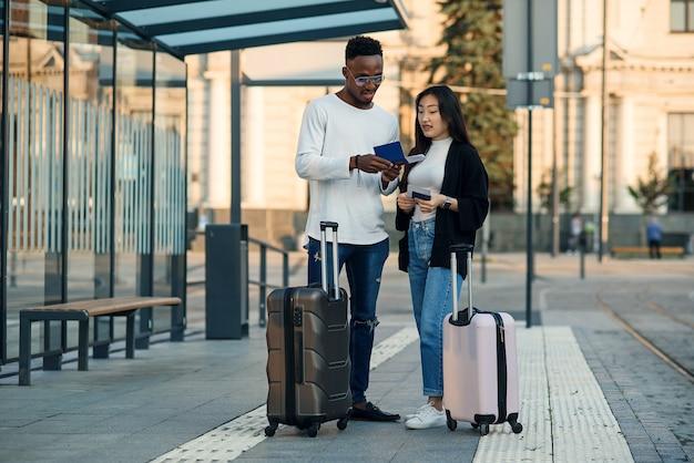 Felice coppia multirazziale guarda la carta d'imbarco controllando l'orario di partenza alla fermata vicino all'aeroporto. concetto di viaggio di vacanze. Foto Premium