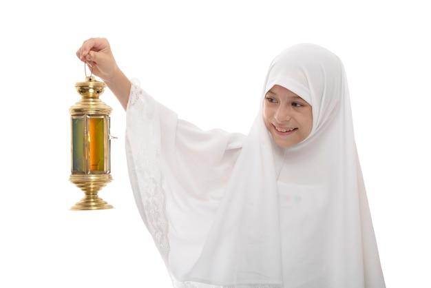 Ragazza musulmana felice che celebra il ramadan con lanterna festiva Foto Premium