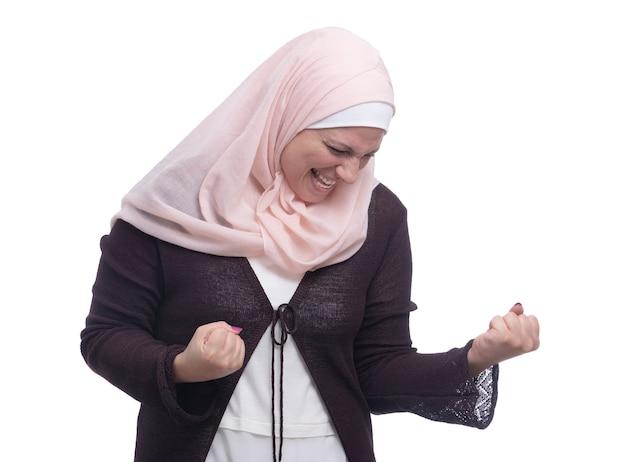 Felice donna musulmana che celebra il trionfo sul muro bianco Foto Premium