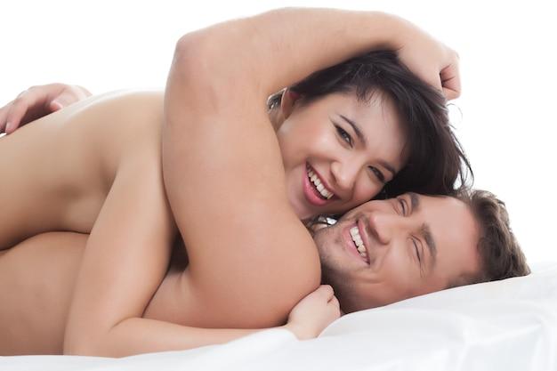 Amanti nudi felici che abbracciano sdraiato a letto, primo piano Foto Premium
