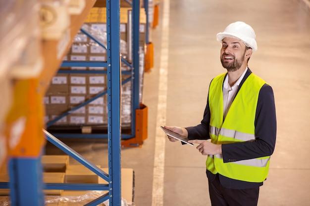 Uomo bello felice guardando gli scaffali di stoccaggio mentre si controlla il processo di lavoro Foto Premium