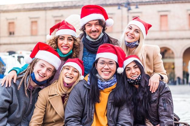 Persone felici con cappelli di babbo natale che celebrano il natale Foto Premium