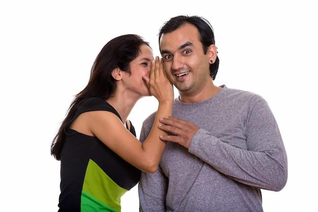 Coppie persiane felici che sorridono mentre la donna che bisbiglia all'uomo Foto Premium