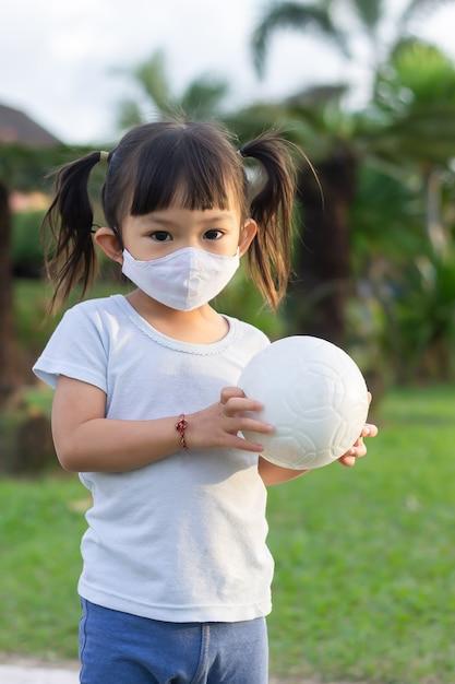 Ragazza asiatica giocosa felice del bambino che porta maschera facciale del tessuto. gioca con la palla nel parco giochi del parco verde. Foto Premium