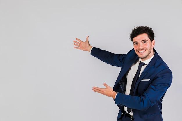 Ritratto felice di un giovane uomo d'affari che dà presentazione contro fondo grigio Foto Premium