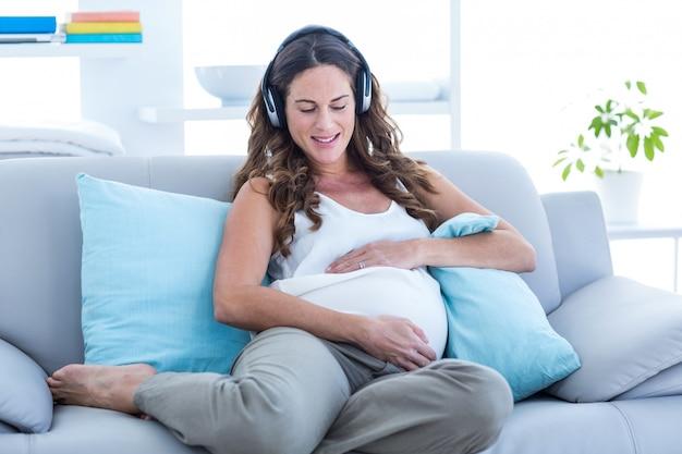 Musica d'ascolto felice della donna incinta sul sofà Foto Premium