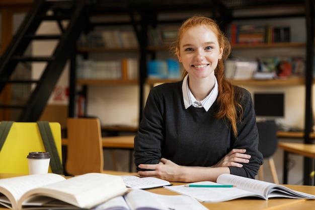 Studente di redhead felice seduto al tavolo con i libri in biblioteca Foto Premium