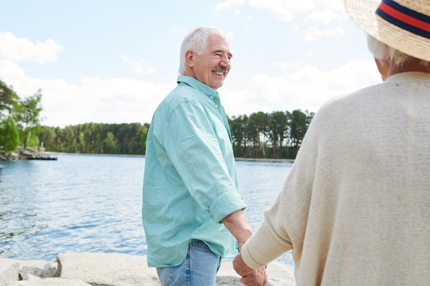 Felice l'uomo anziano in abbigliamento casual che tiene la moglie per mano mentre entrambi trascorrono il fine settimana in riva al lago nel paese Foto Premium