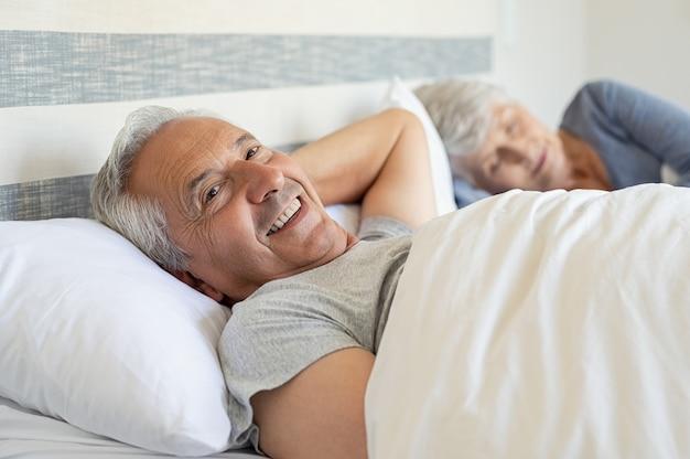 Uomo senior felice che si trova sul letto Foto Premium