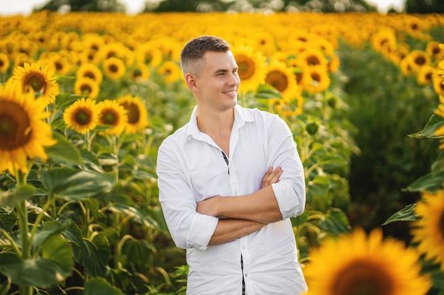 Coltivatore sorridente felice che sta fiero davanti al suo giacimento dei girasoli Foto Premium