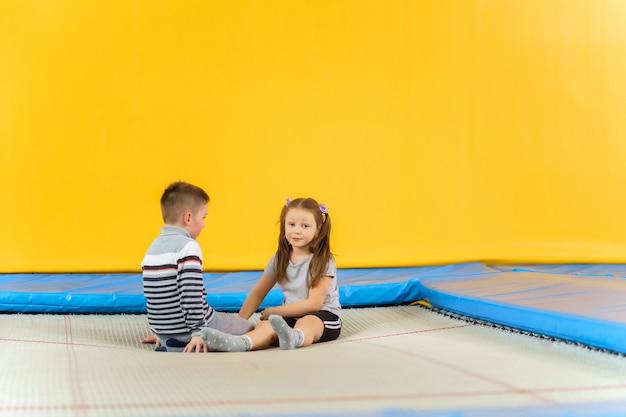 Piccoli bambini sorridenti felici che si siedono sul trampolino dell'interno e che giocano nel centro di intrattenimento Foto Premium