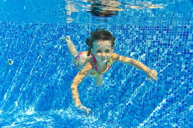 Felice sorridente bambino subacqueo in piscina, bella ragazza nuota e divertirsi. sport per bambini in vacanza estiva in famiglia. vacanza attiva Foto Premium