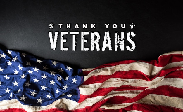 Felice giorno dei veterani concetto. bandiere americane contro una lavagna Foto Premium
