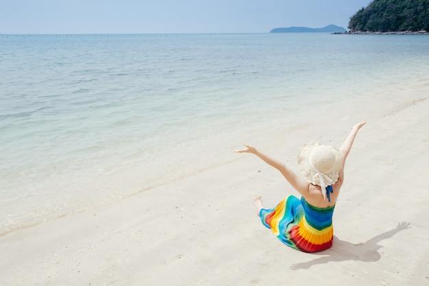 Donna felice sul cielo della spiaggia e delle nuvole. Foto Premium