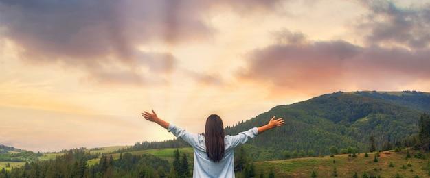 Donna felice che gode del tramonto stando in piedi sulla cima della montagna Foto Premium