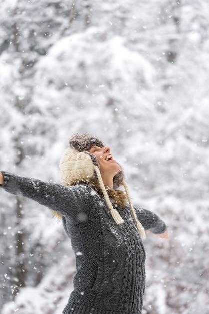 Donna felice a neve che cade a braccia aperte Foto Premium