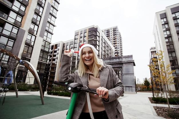 La donna felice cavalca uno scooter elettrico affittato alla festa di natale. sta riparando il suo cappello rosso di babbo natale e ridendo. vita urbana della città. giovane donna bionda allegra in cappotto casual andando a incontrare gli amici. Foto Premium