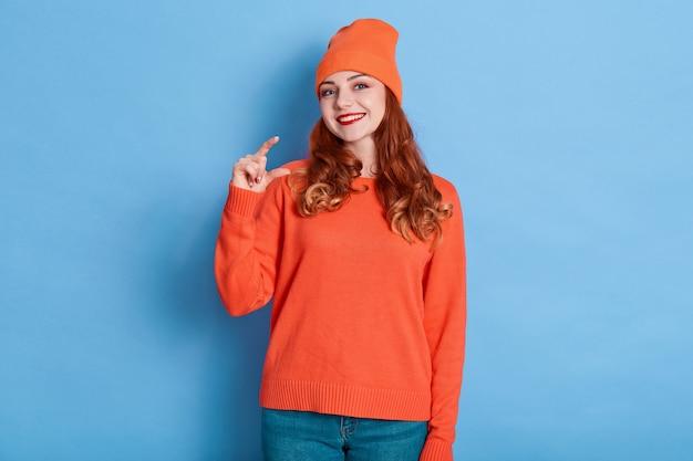 La donna felice mostra un piccolo gesto, dimostra pochi centimetri o un sentimetro, vestita con abiti casual. Foto Premium