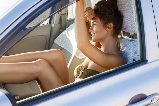 Donna felice che si siede in macchina Foto Premium